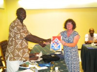 A Rotarian in the Gambia receives a banner from Stella Elliott